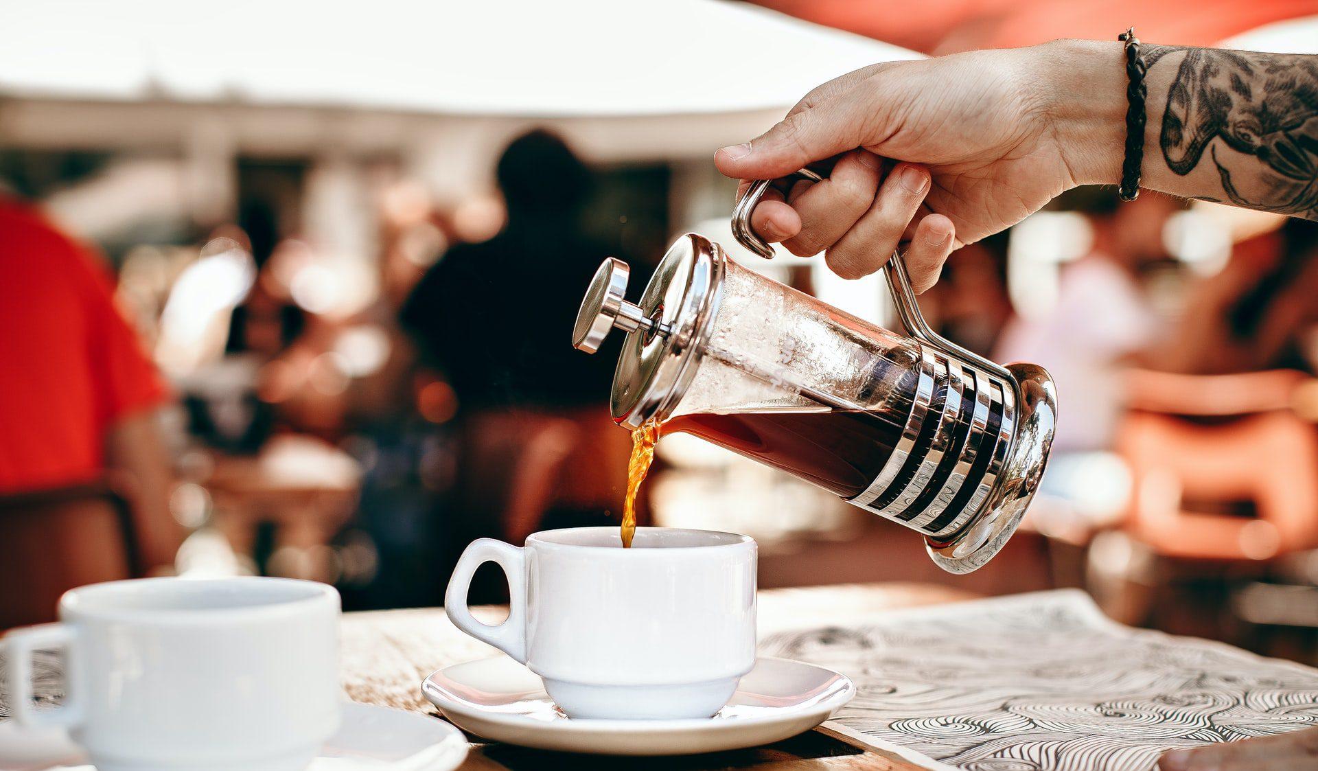 Barista sirviendo café de una prensa francesa en una taza blanca
