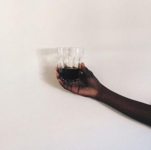 holding a glass of coffee against a white wall