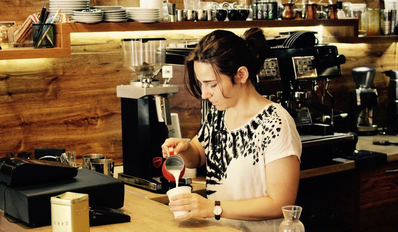 Barista vertiendo leche en una taza de cafe