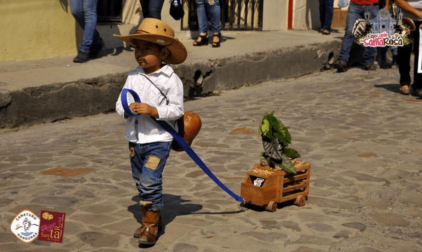 niño desfila en un evento de cafe en Honduras