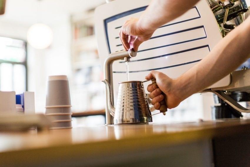 barista saca agua caliente para preparar un filtrado