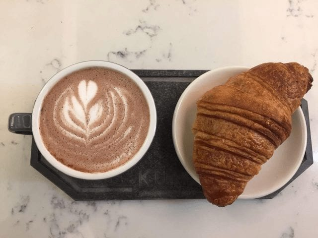 taza de cafe acompanado de croissant