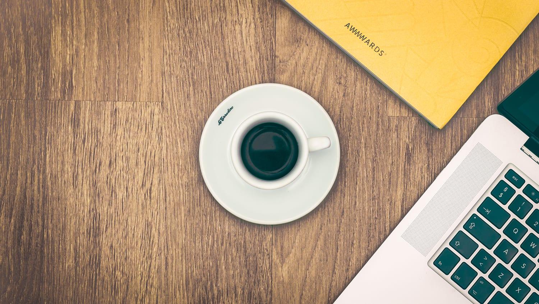 coffee cup on desk; looks like camera lens