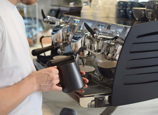 un barista vrema leche para cappuccino