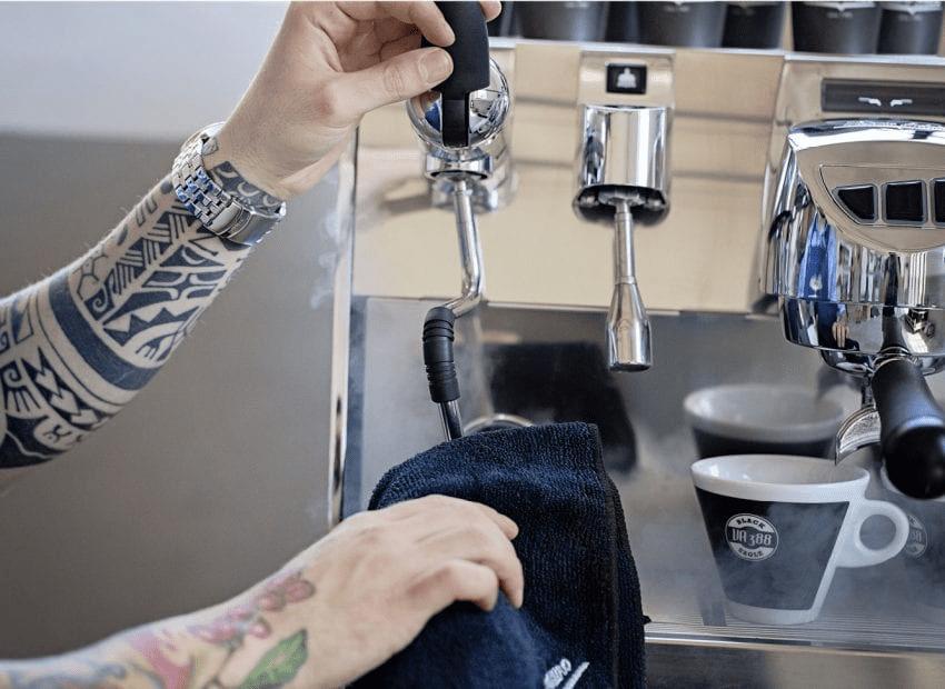 barista limpia lanzeta de maquina espresso