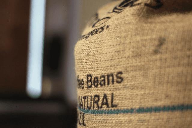 Granos de cafe verde en un saco