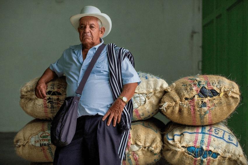productor junto a sus sacos de cafe listos para vender