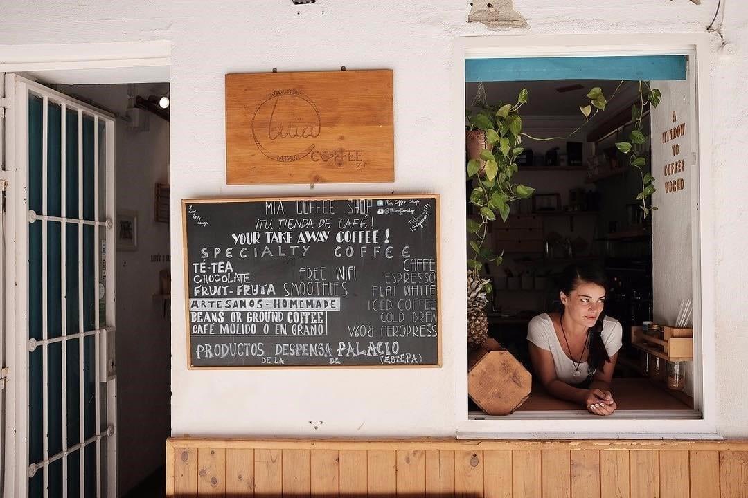 una tienda de cafe con una ventana muy bella en la esquina