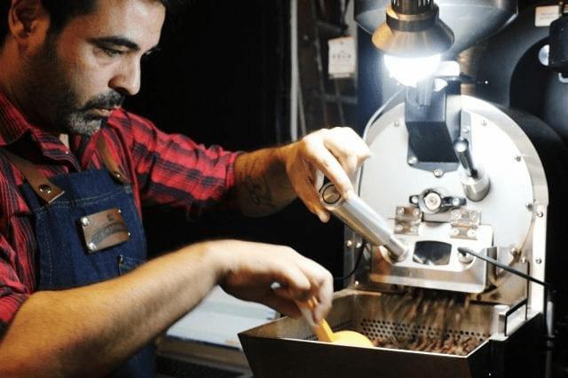 un tostador revisando la tostion de sus cafes