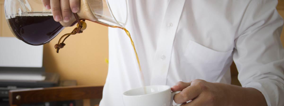 Barista sirviendo café preparado en chemex en una taza blanca