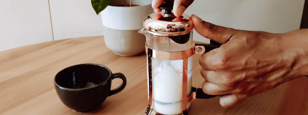 Persona texturizando leche con una prensa franesa