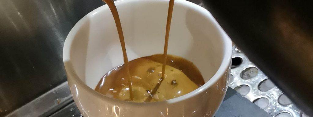 Espresso cayendo en una taza blanca
