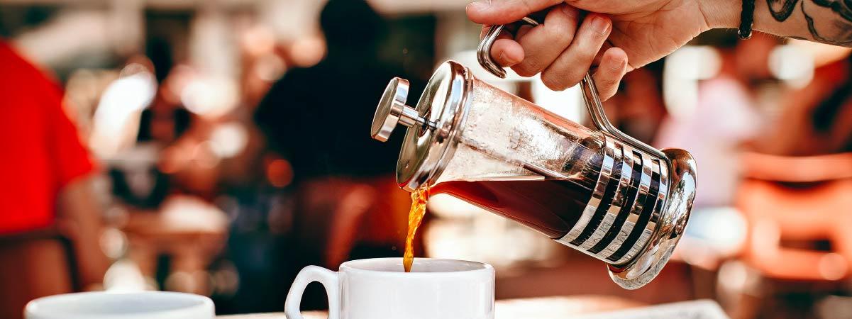 Barista sirviendo café con una prensa francesa en una taza blanca
