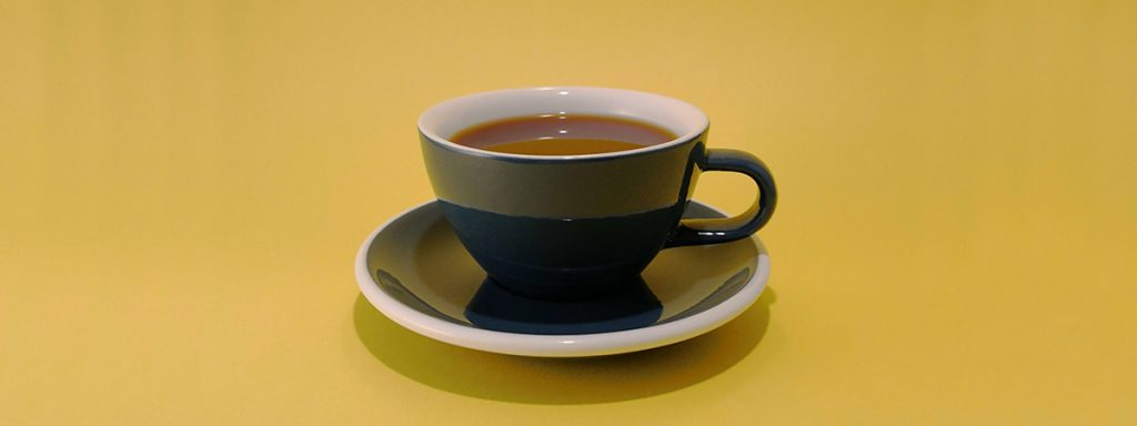 taza negra con un americano en un fondo amarillo