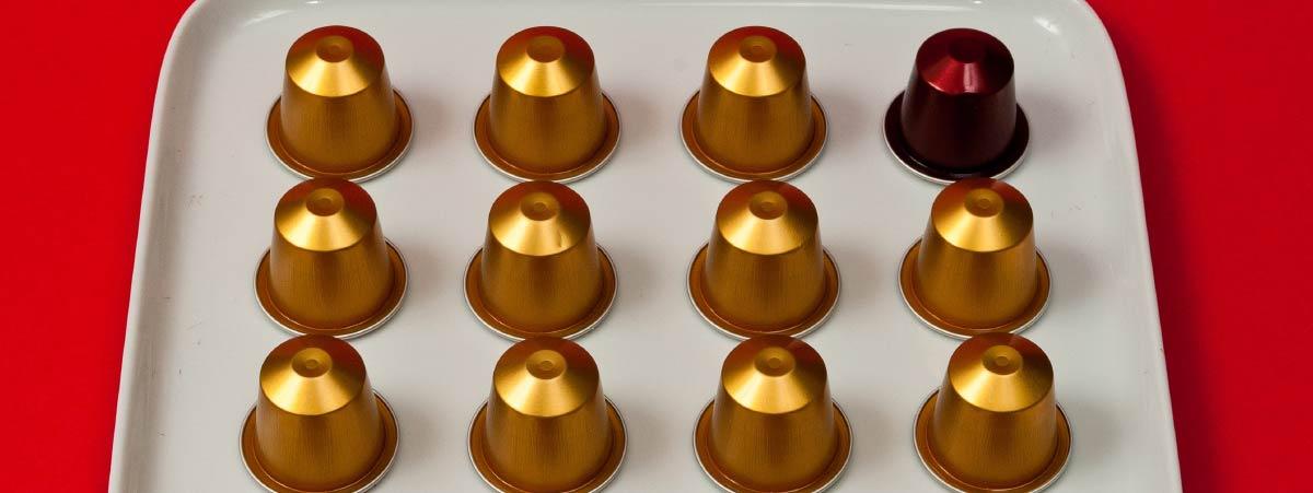 Bandeja balnca con capsulas de café doradas