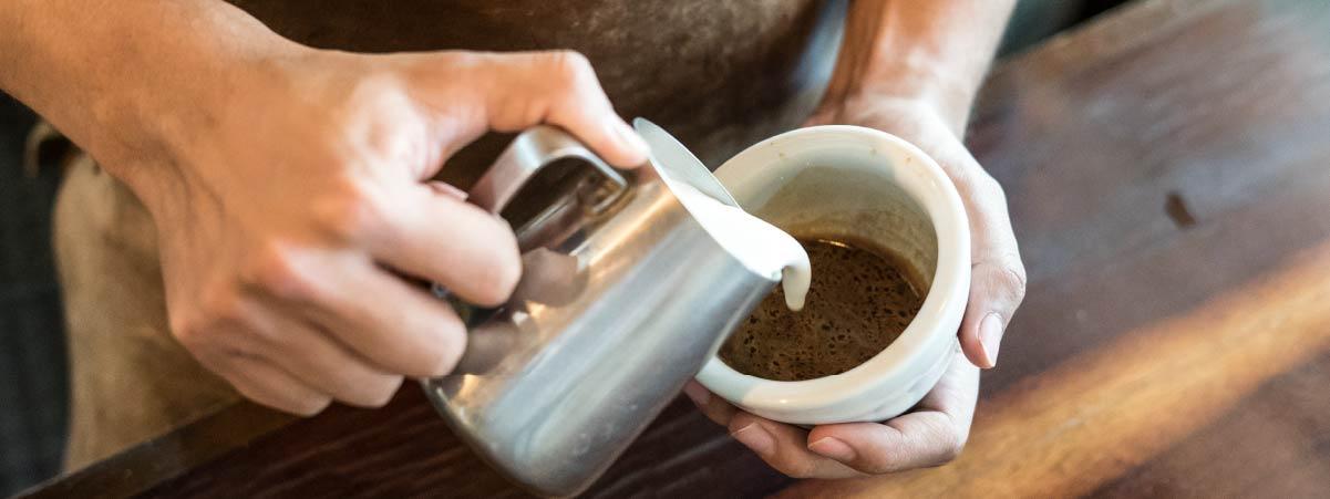 Barista sirviendo leche en una taza blanca con un shot de espresso