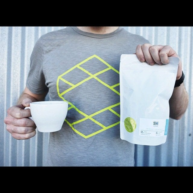 Man holding a cup and a bag of coffee