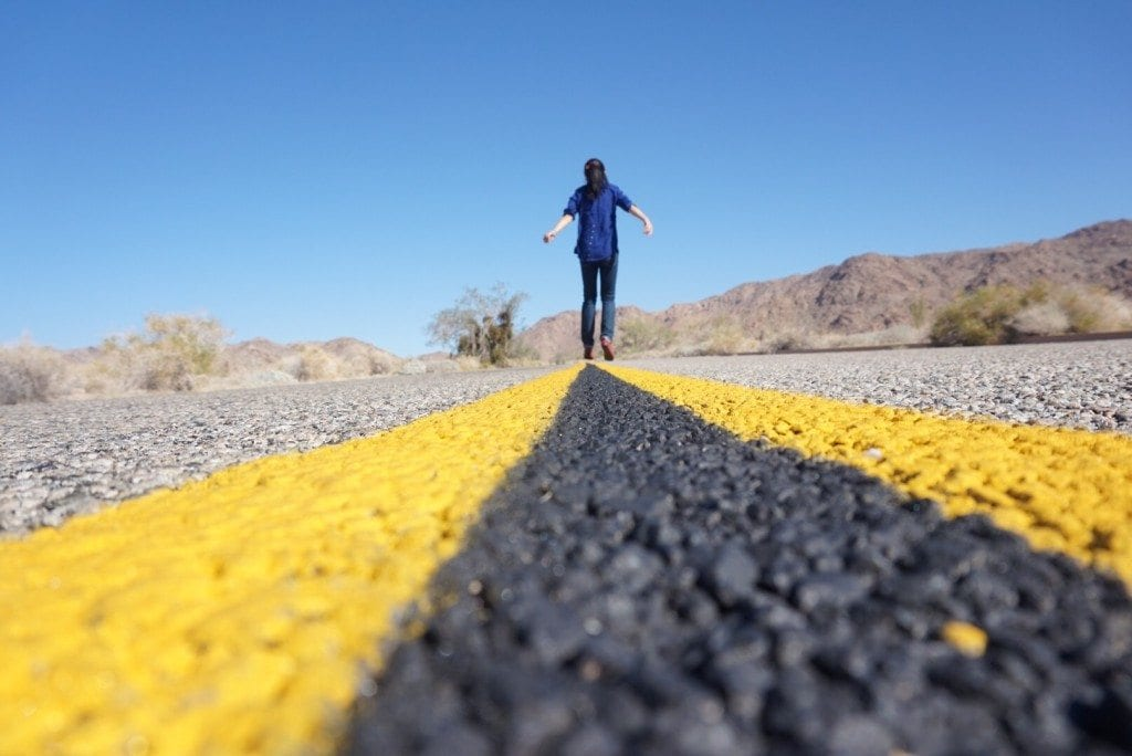 Woman walking on a road in the sun