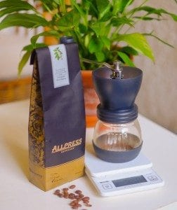 handgrinder, scale and a bag of coffee