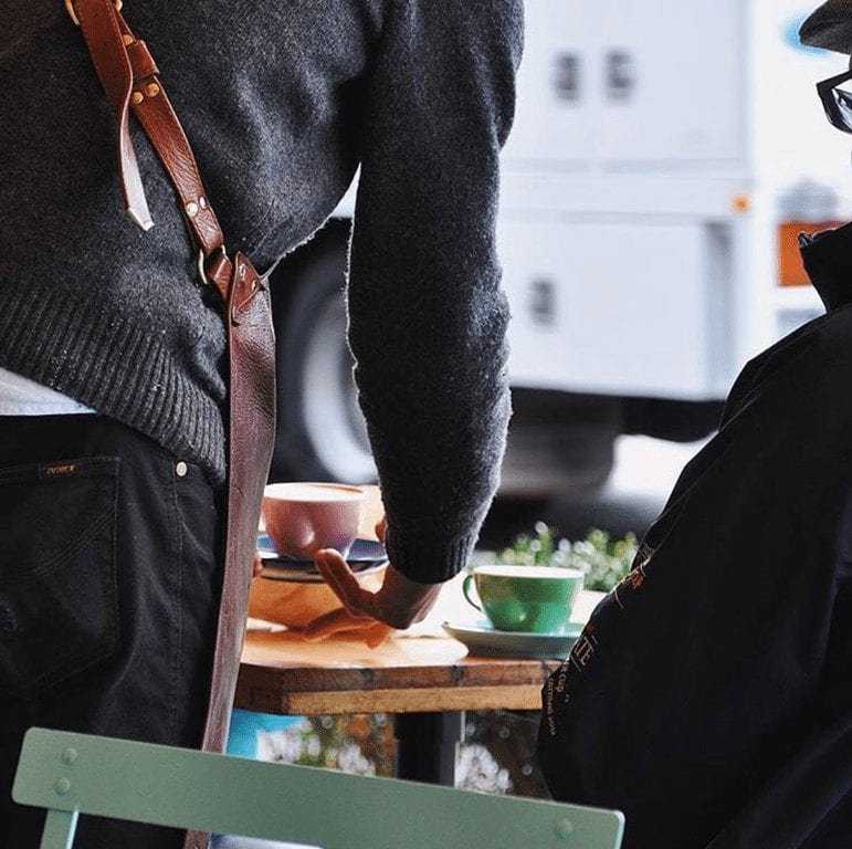 Barista serving coffee to a customer