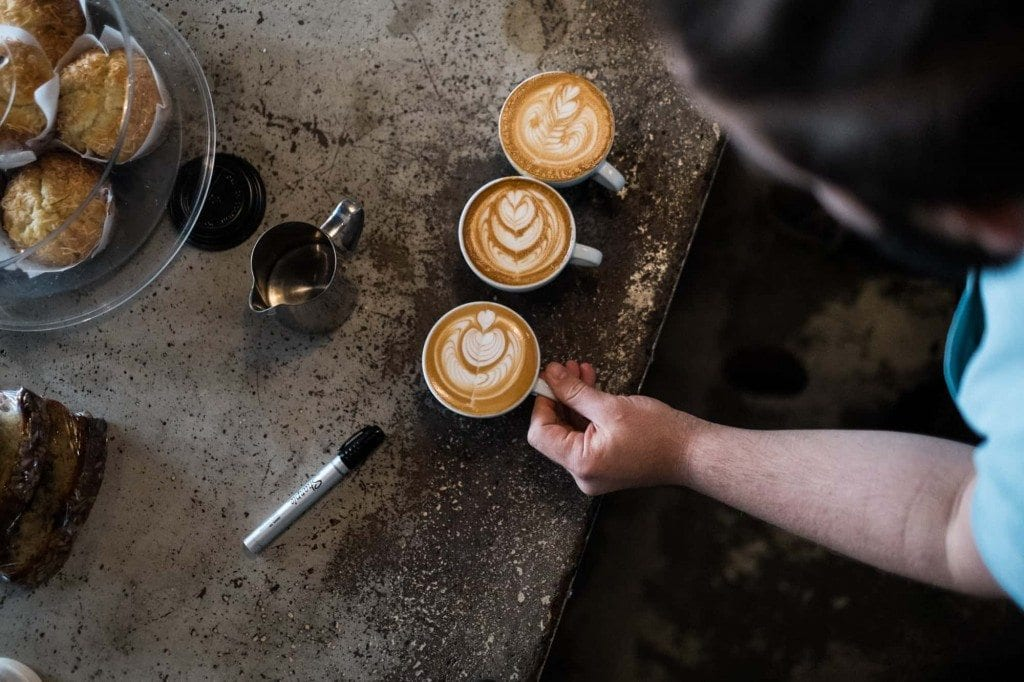 three cappuccinos on concrete bar