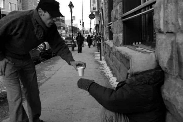 man giving coffee to homeless man
