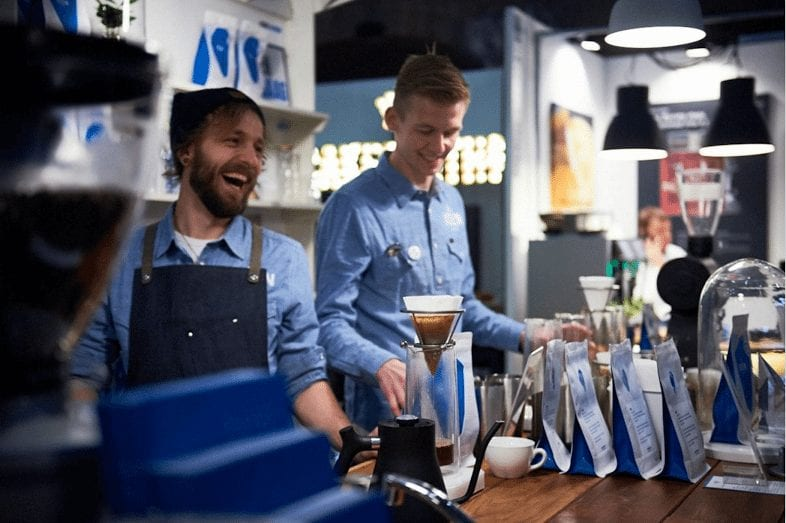 Two baristas laughing at a Keen Coffee brew bar
