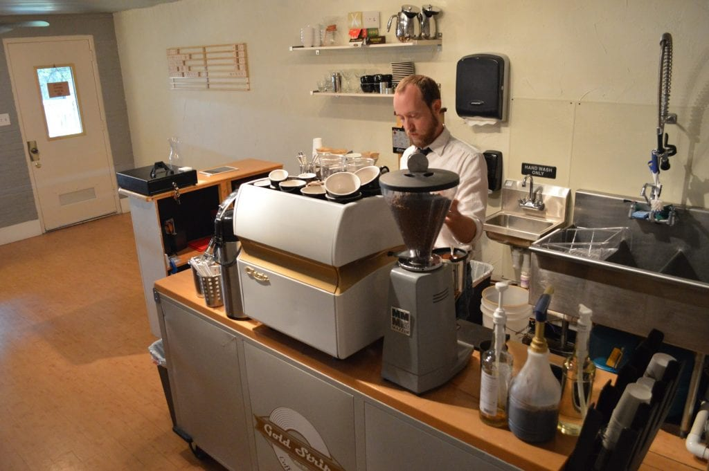Barista behind the bar in Gold Stripe Coffee