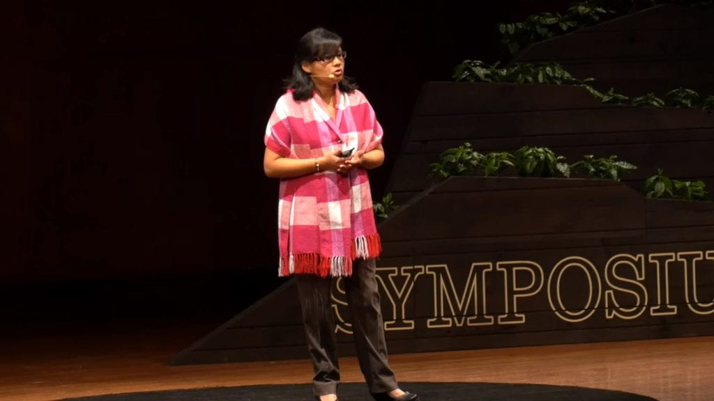 Mayra Orellana-Powell on stage at Re:co Symposium