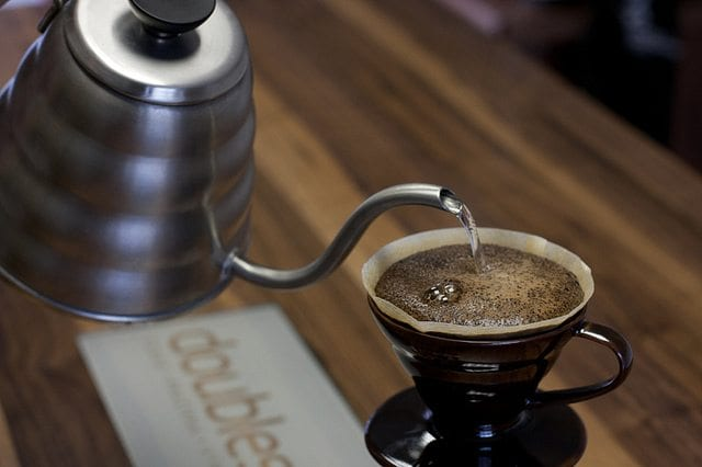 Someone pours water into a V60 to brew coffee