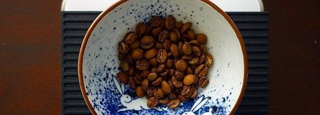 Roasted coffee beans in a ceramic bowl