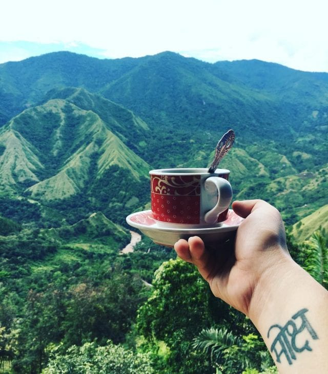 Person with a red cup of coffee with mountains in the background