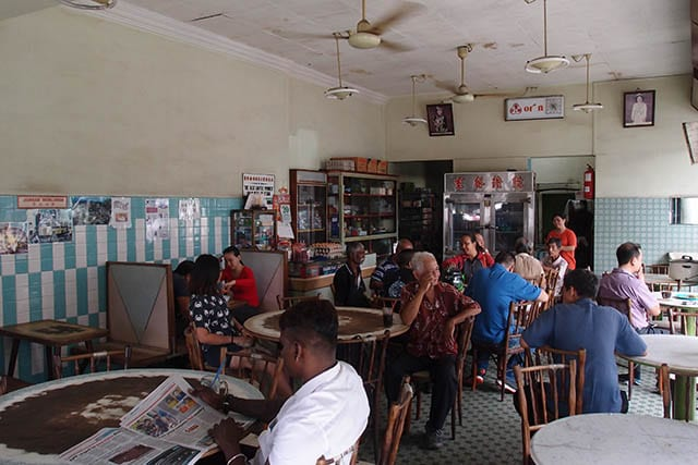 People eat breakfast in a kopi tiam