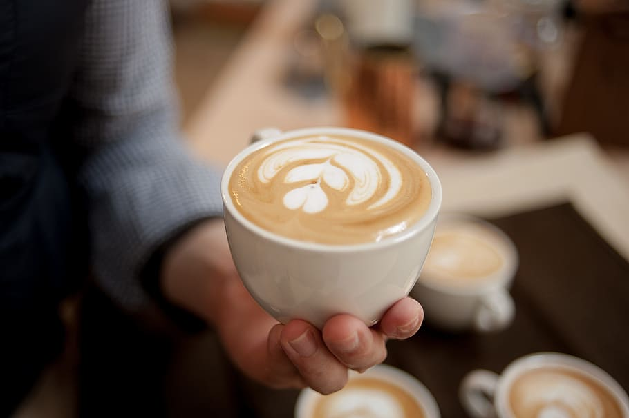 Barista holdig a flat white in a white cup