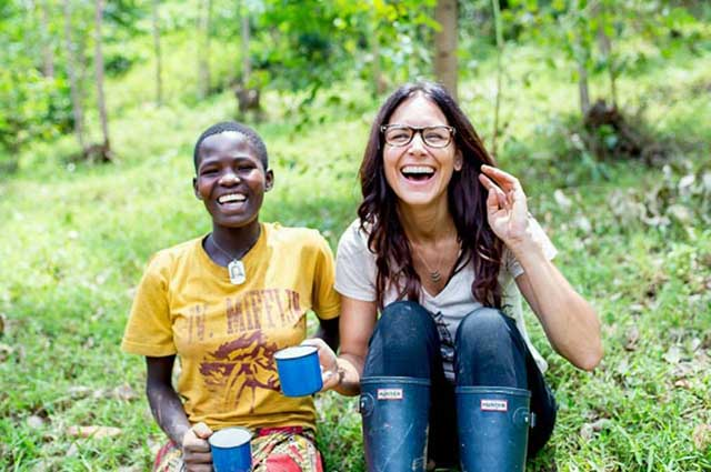 Two laughing women drink coffee in a forest