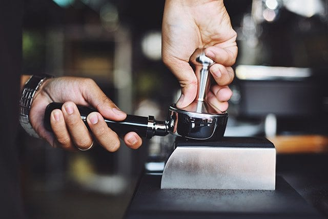 Barista tamps coffee