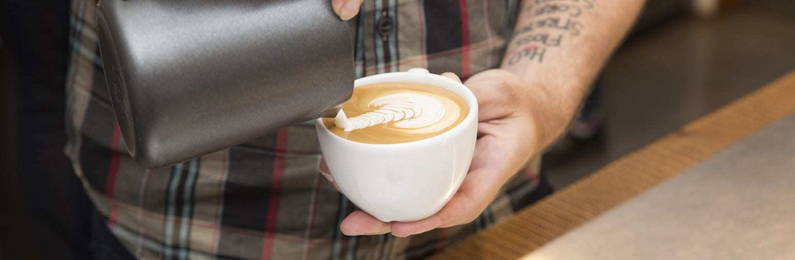 Barista pouring Milk to make an arte latte