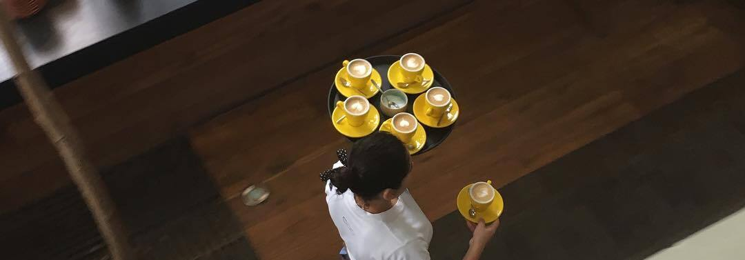 Barista serving flat white in yellow cups