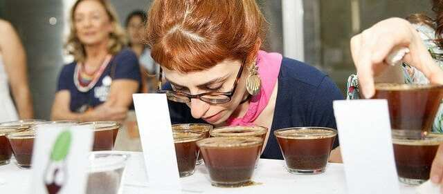 Woman evaluating the aroma in a cupping