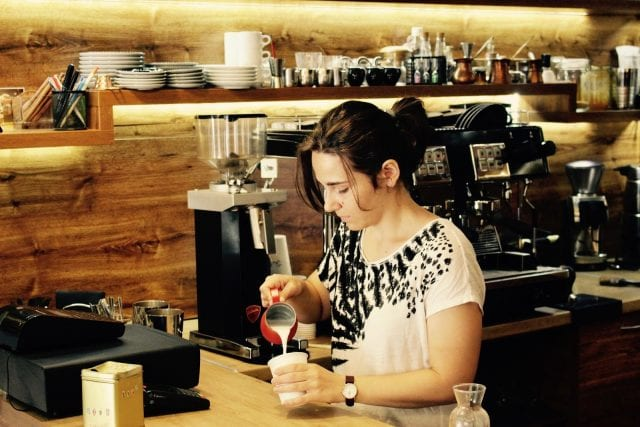 Barista making arte latte in a disposable cup