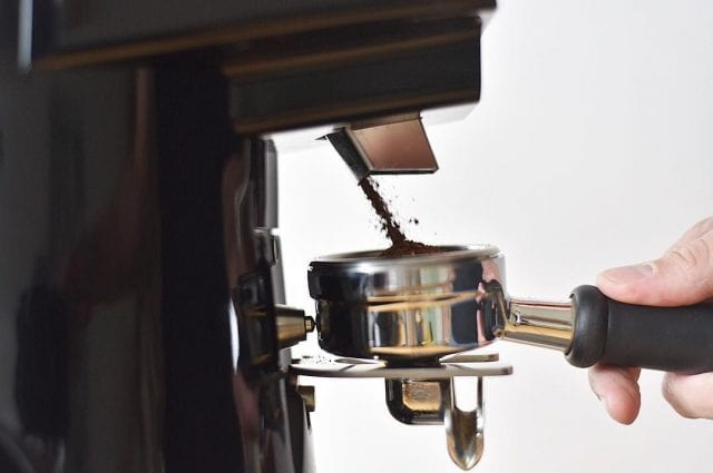 Barista grinding coffee for an espresso