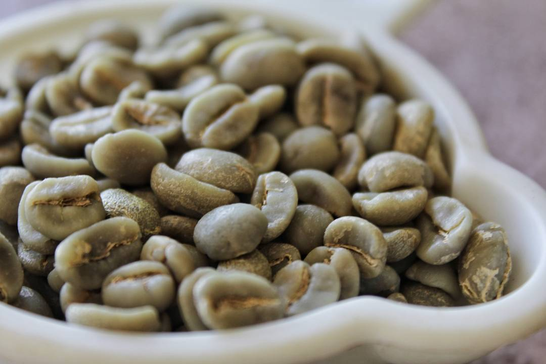 green coffee beans in a ceramic bowl
