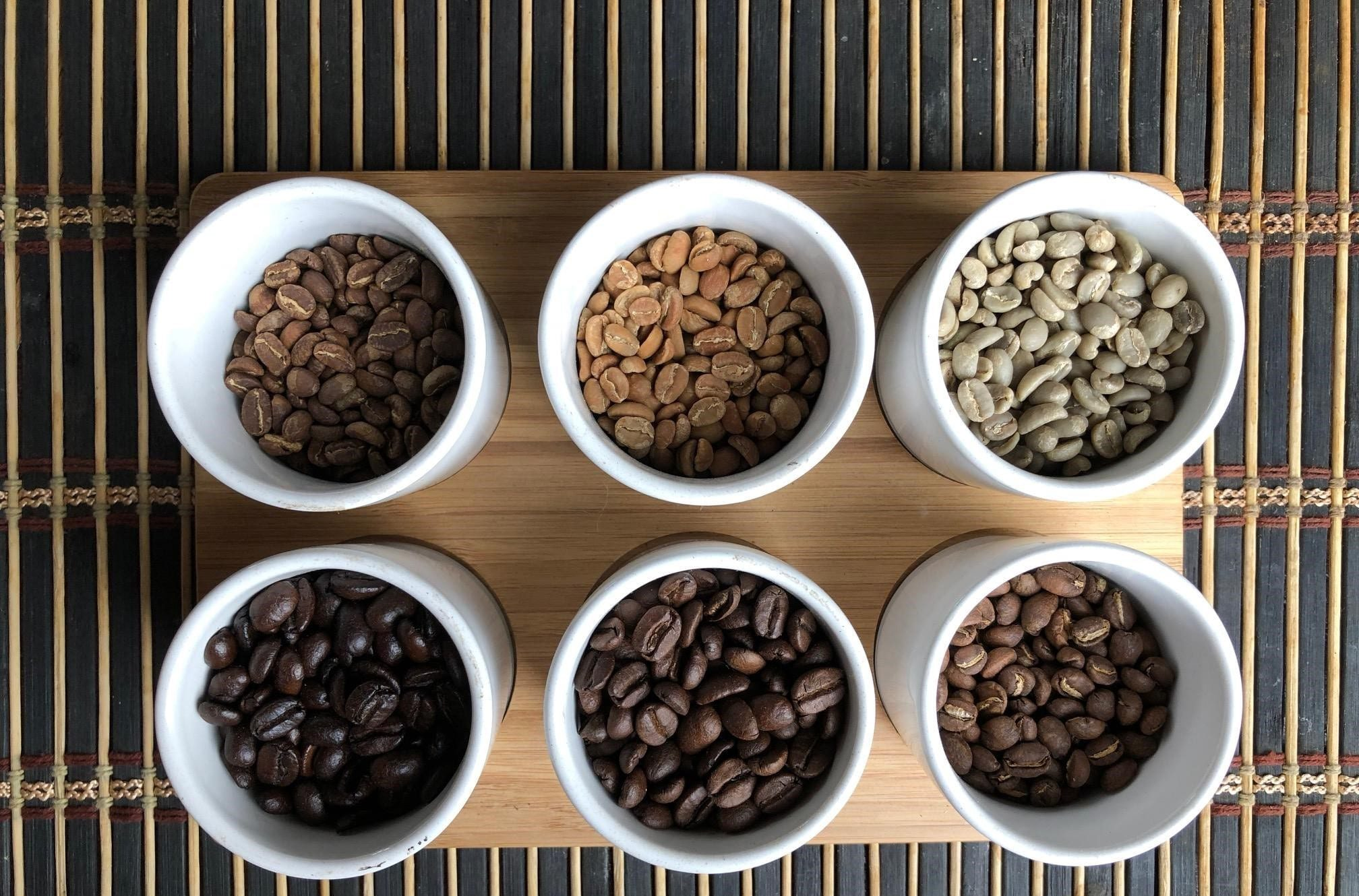 Different samples of drakness of coffee beans in white cups in a woodes tray