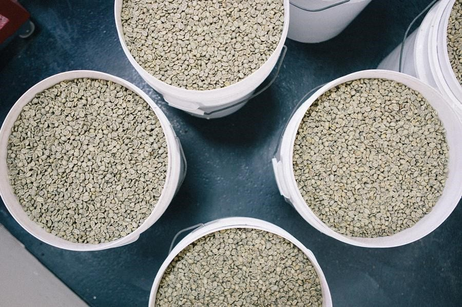 White cans full of green coffee beans
