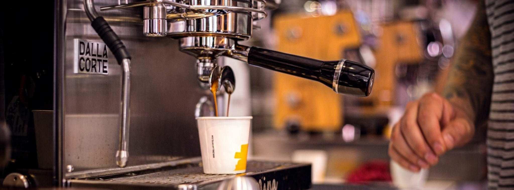 Barista making an espressoo with Dalla Corte espresso machine in a disposable cup