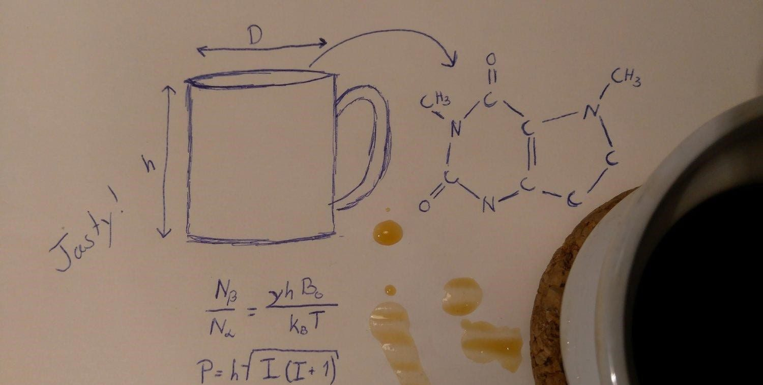 Coffee chemical formula drawed in a sheet with a cup of coffee