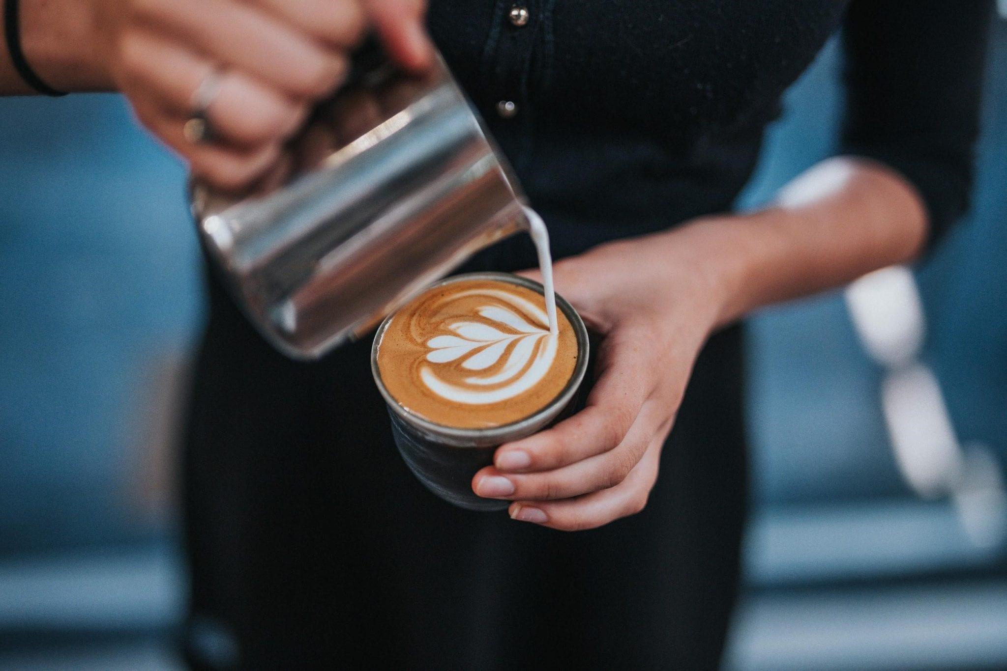Barista vertiendo arte latte