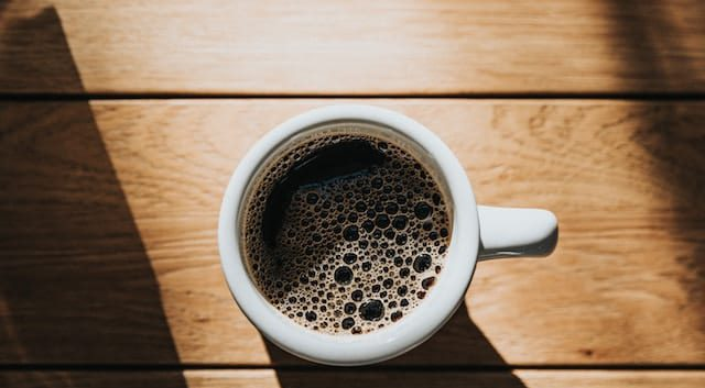 White cup with coffee in a wooden surface