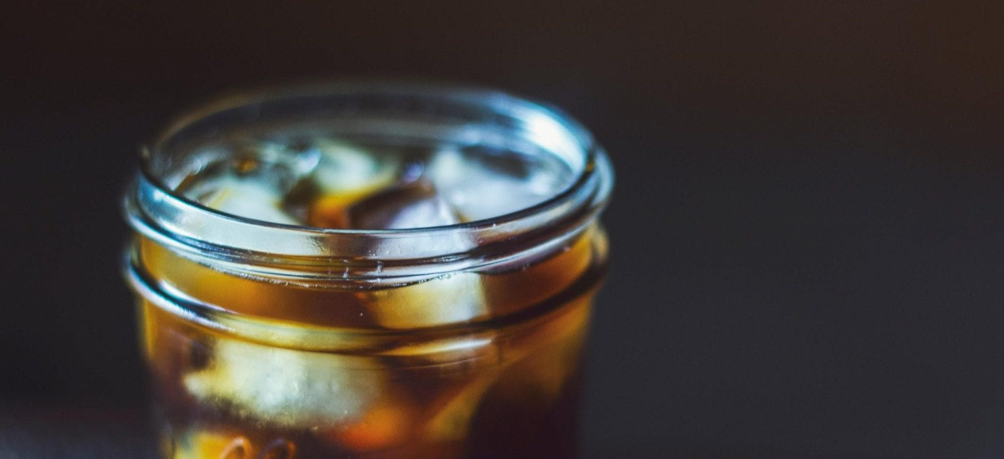 Glass of iced coffee on a black background