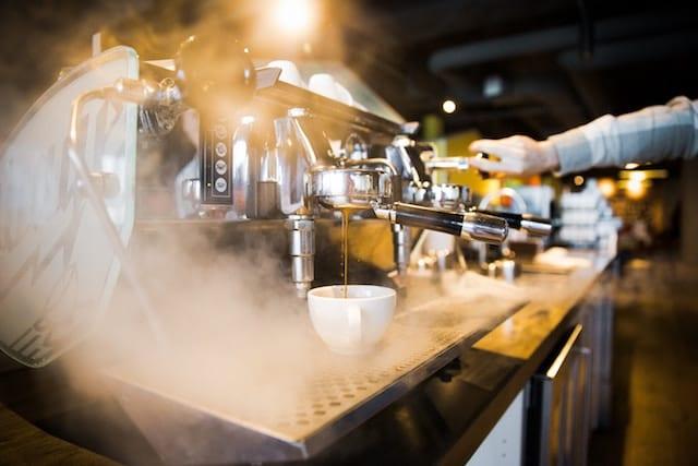 Um barista trabalhando com uma máquina de espresso.
